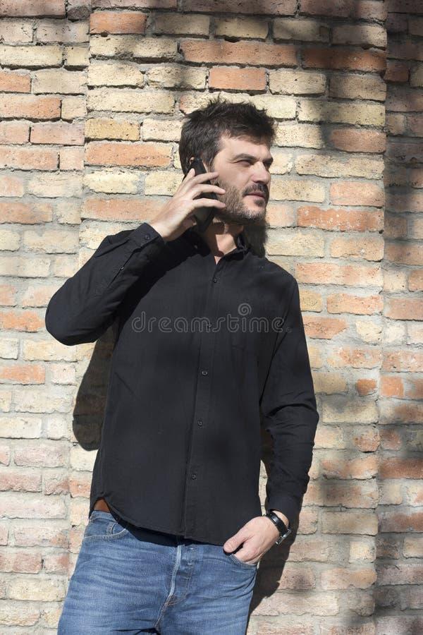 在巧妙的电话的年轻都市商人在街道谈话在smar 免版税库存照片