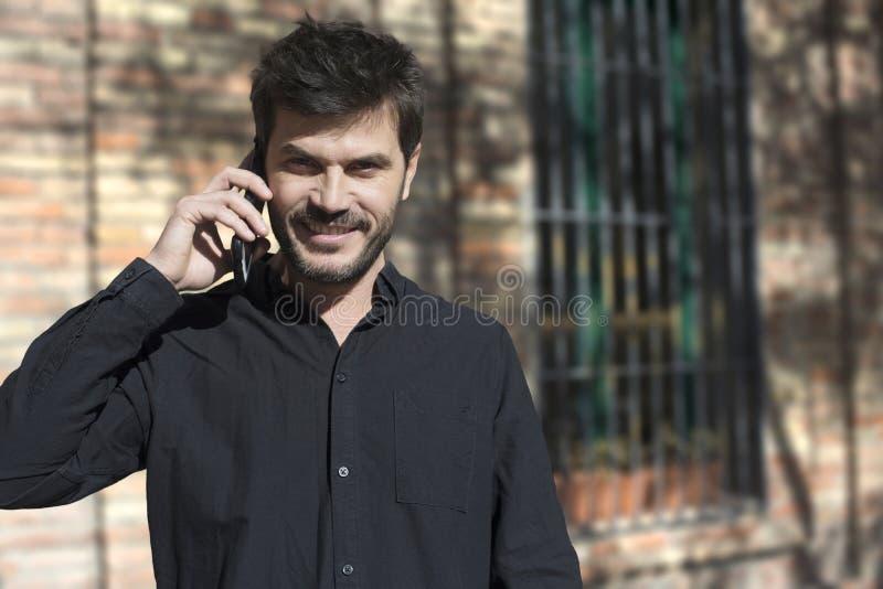 在巧妙的电话的年轻都市商人在街道谈话在smar 图库摄影