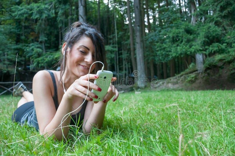 在巧妙的电话的美好的女孩戏剧在公园 免版税库存照片