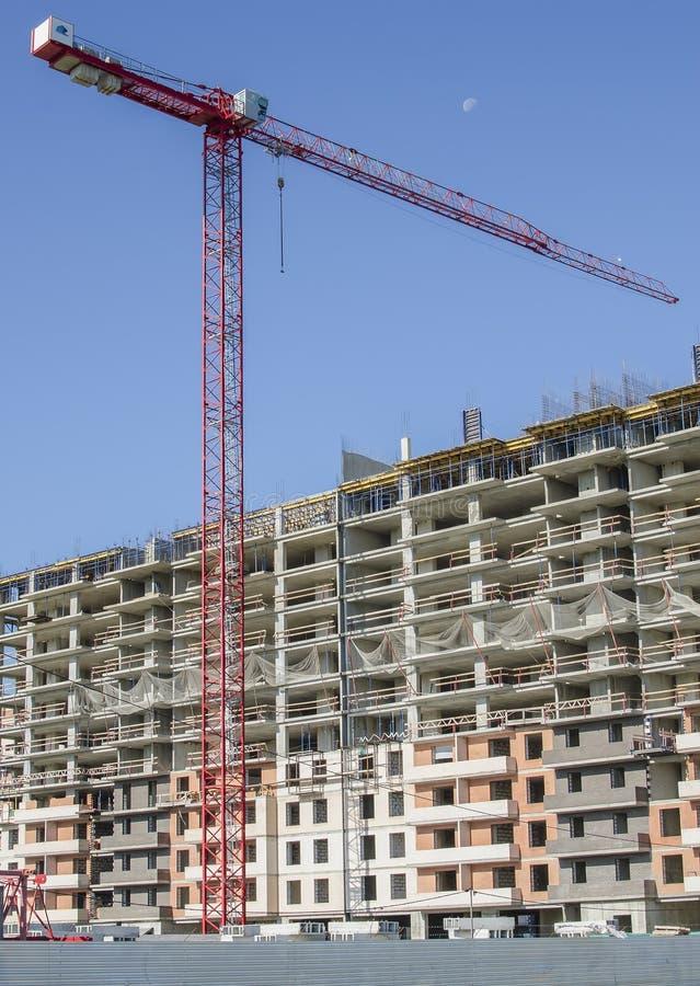 在巨型独石砖房子背景的高空起重机  免版税库存图片