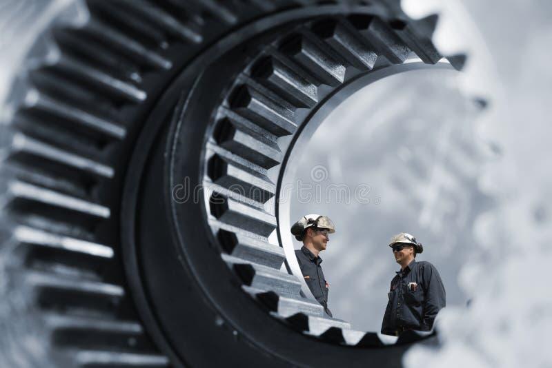 在巨型齿轮里面的产业工作者 免版税库存照片