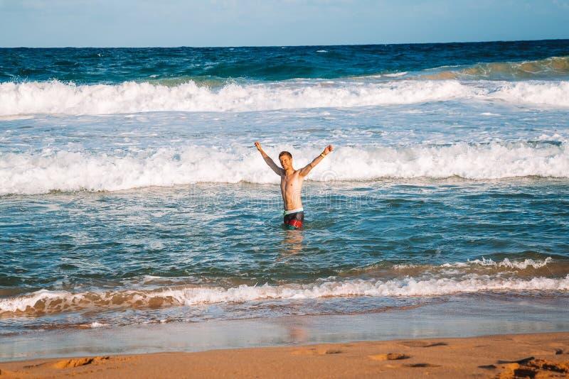 在巨大的波浪的年轻人游泳 免版税库存图片