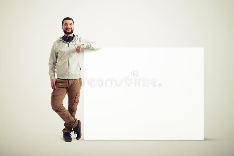 在巨大的海报附近的人在白色背景 免版税库存照片