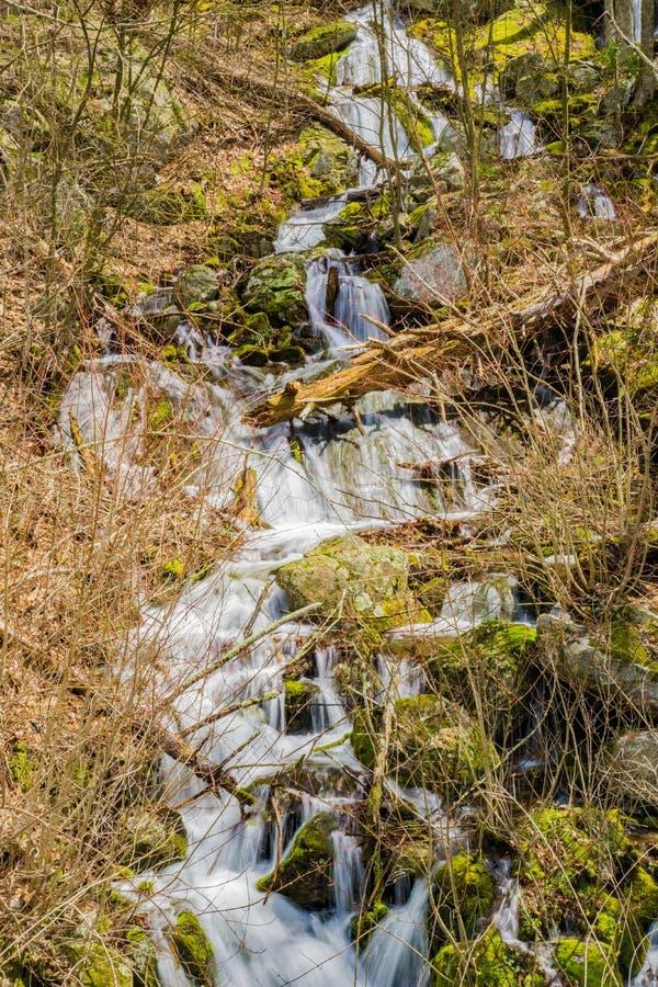在巨石城领域的垂直的落下的山瀑布 免版税库存图片
