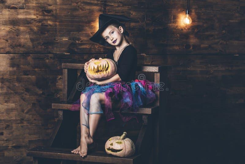 在巫婆服装的女孩childl用南瓜和糖果在霍尔 库存照片