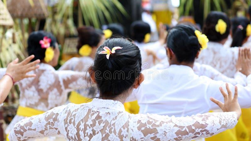 在巴厘岛印度尼西亚,宗教仪式的印度庆祝有黄色和白色颜色的,妇女跳舞 库存照片