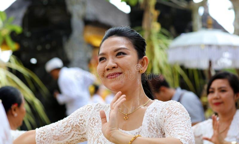 在巴厘岛印度尼西亚,宗教仪式的印度庆祝有黄色和白色颜色的,妇女跳舞 免版税库存照片