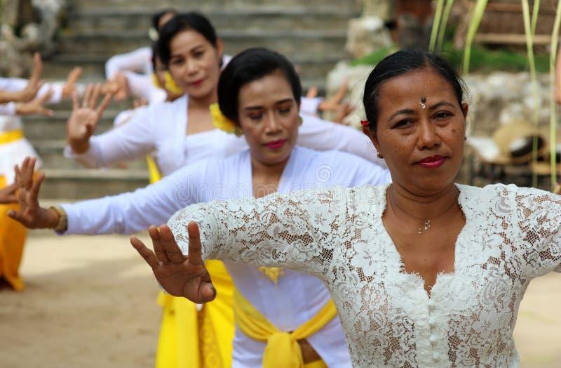 在巴厘岛印度尼西亚,宗教仪式的印度庆祝有黄色和白色颜色的,妇女跳舞 免版税库存图片