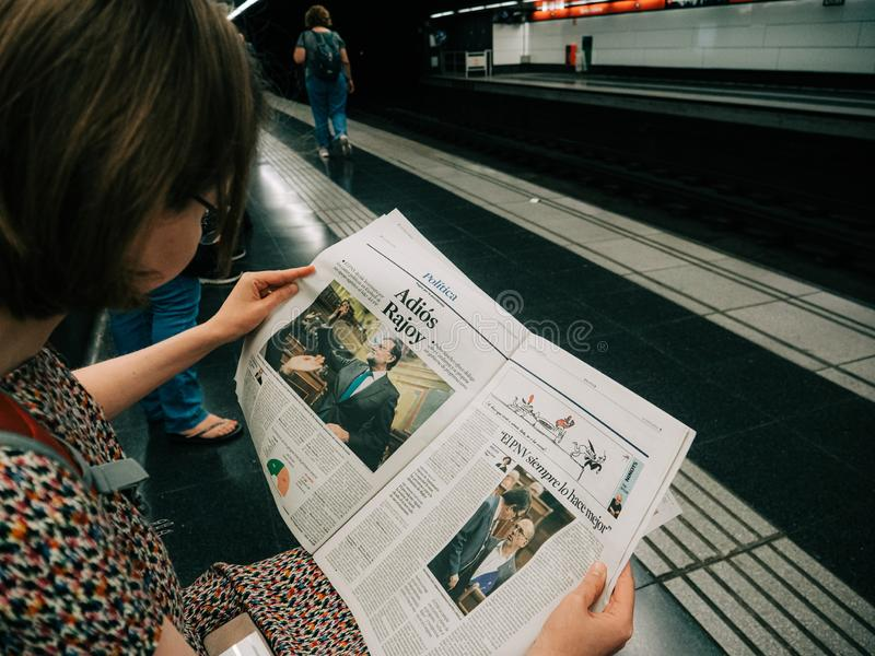 在巴塞罗那地铁车站的妇女读书La Vanguardia Raojoy辞职 库存照片