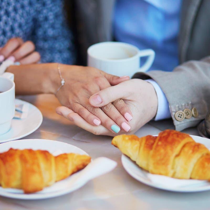 在巴黎人咖啡馆,饮用的咖啡的夫妇用新月形面包和举行手 库存照片
