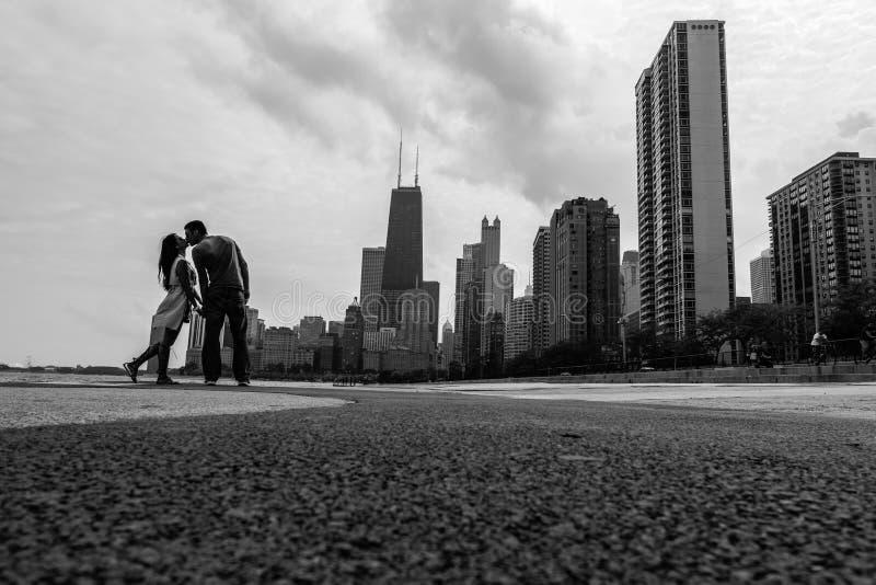 在市的地平线的前面夫妇亲吻芝加哥 免版税图库摄影