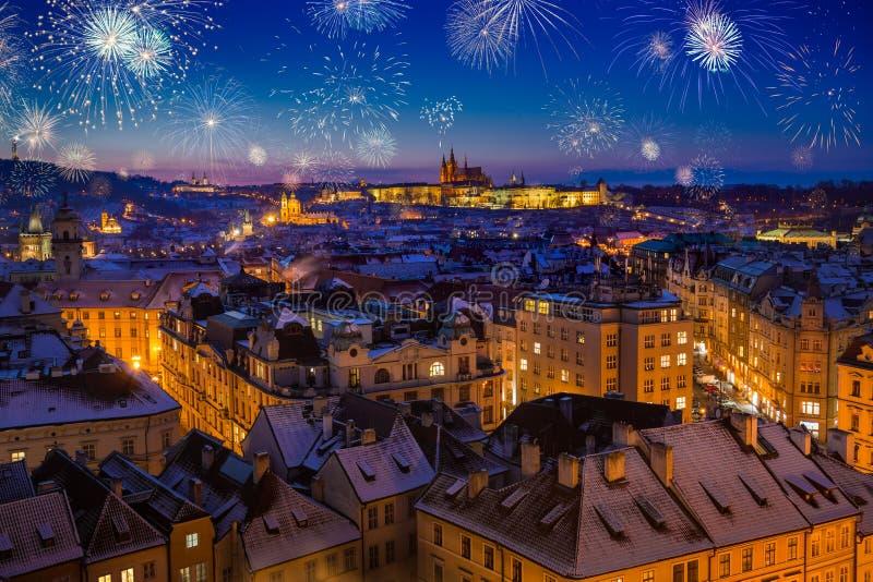 在布拉格城堡上的烟花与在晚圣诞节日落期间的多雪的屋顶 图库摄影