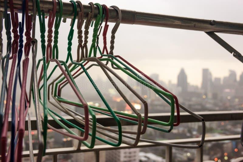 在布料的衣架在居民住房阳台排行在一个雨天有模糊的城市视图背景,不可能洗涤 免版税图库摄影