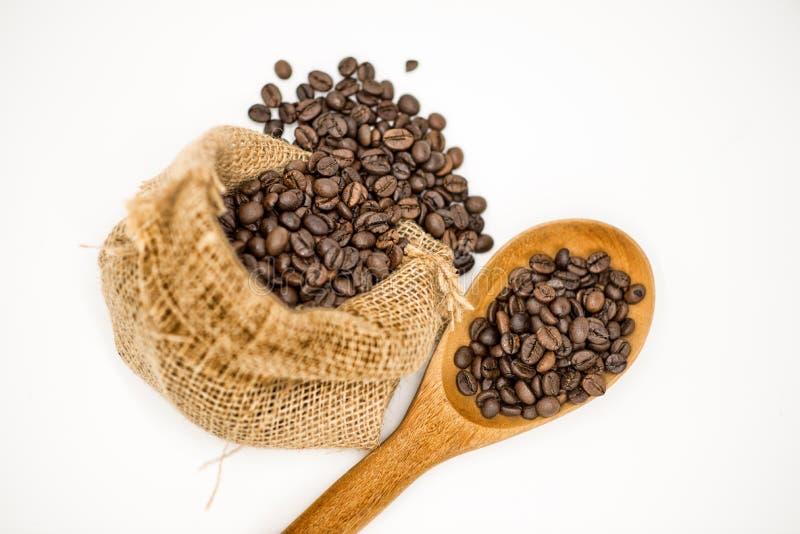 在布料袋子和木匙子的咖啡豆 免版税库存照片
