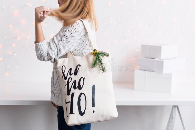 在布料袋子的无法认出的妇女藏品圣诞礼物 节日快乐冬天 Christmastime庆祝的礼物 免版税库存照片