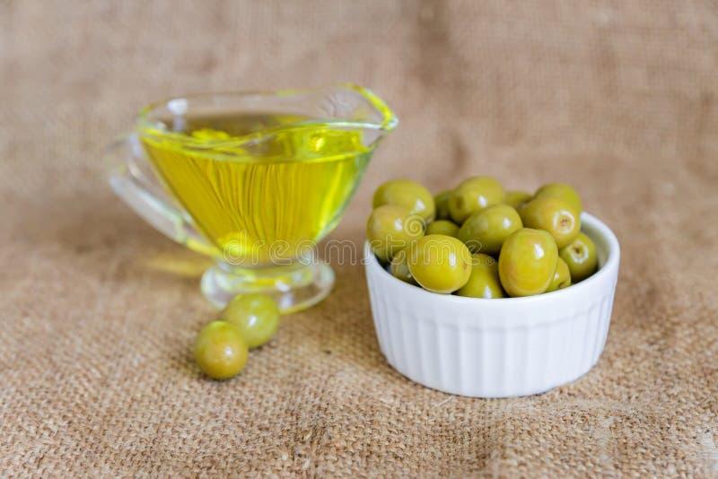 在布背衬上的白色陶瓷碗中用特级初榨橄榄油和新鲜绿色橄榄制作的玻璃平底锅 库存照片