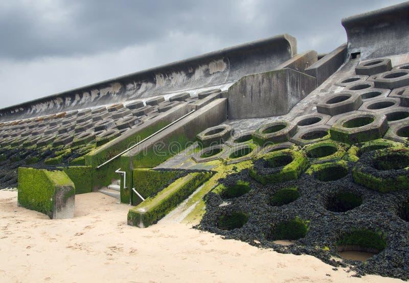 在布莱克浦南部的防波堤修建了与导致海滩的步的具体蜂窝类型结构盖了海草 库存照片