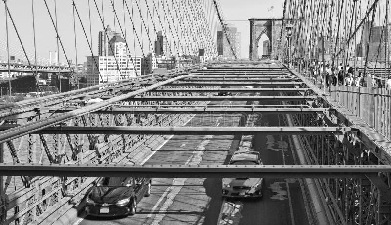 在布鲁克林大桥和哈得逊河的看法有连续的汽车的和现代地平线在背景中在曼哈顿,纽约 免版税库存照片