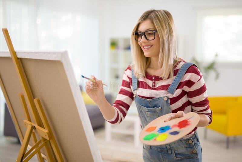 在帆布的女性艺术家绘画 免版税库存图片