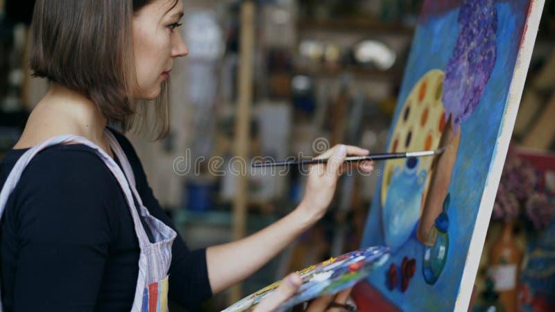 在帆布的年轻艺术家妇女绘画静物画图片在艺术学校 图库摄影