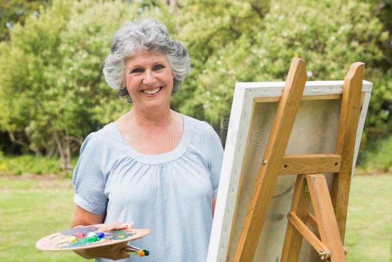 在帆布的愉快的成熟妇女绘画 库存照片