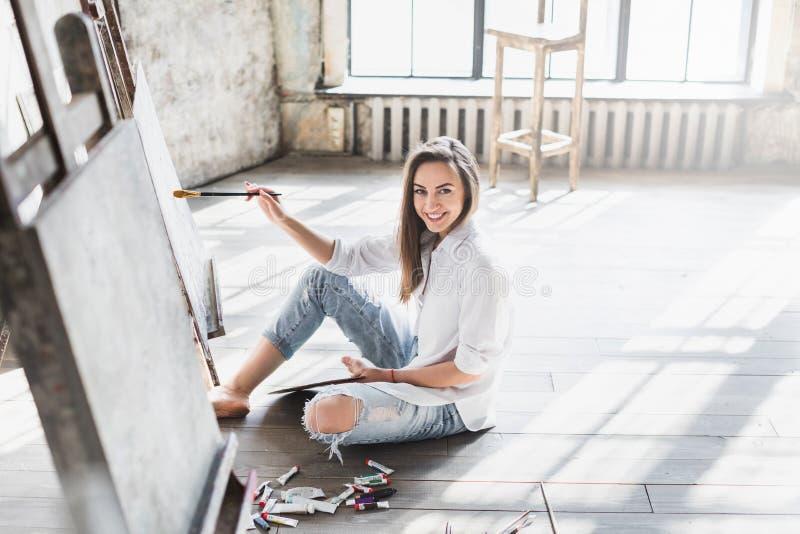 在帆布的画象专业女性艺术家绘画在演播室 库存照片