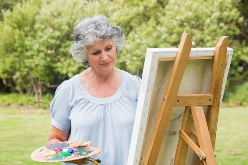 在帆布的美满的成熟妇女绘画 库存照片