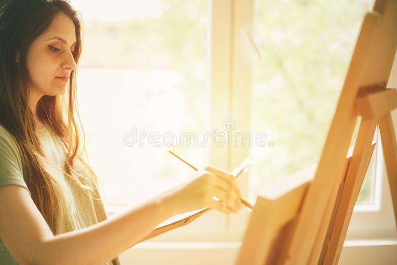 在帆布的年轻女性艺术家绘画 库存图片