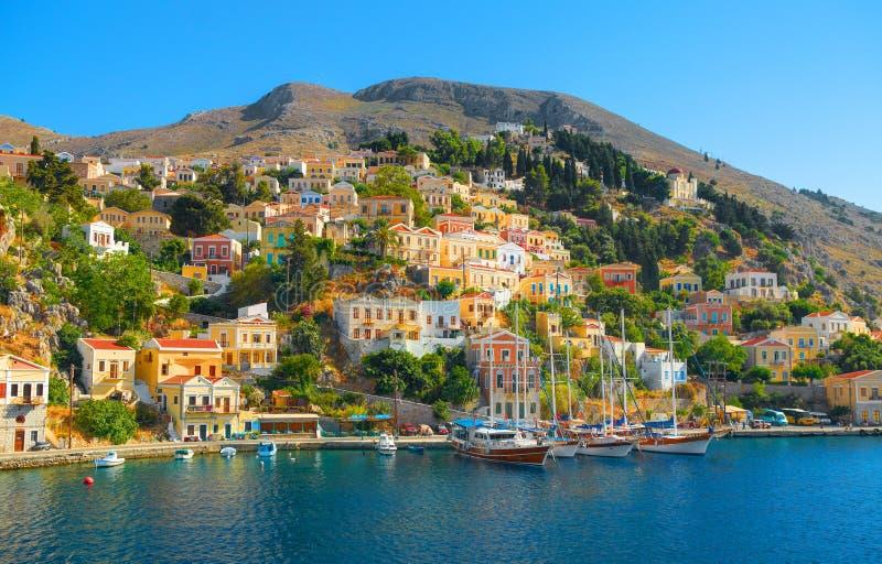 在希腊海锡米岛海岛港口口岸的看法,古典船乘快艇,海岛小山的,游人爱琴海海湾房子 希腊islandsV 免版税库存图片