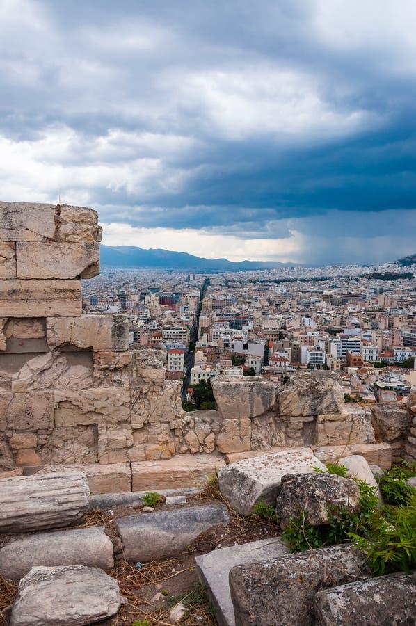 在希腊首都雅典市的全景都市风景视图从上城小山 看法通过在平直的街道上的古老被破坏的石头 免版税库存照片
