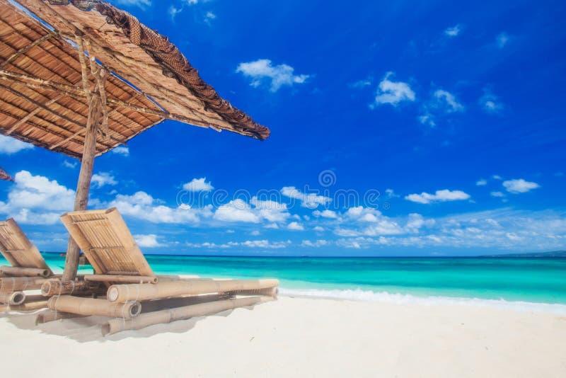 在帐篷下的躺椅在海滩 免版税库存照片