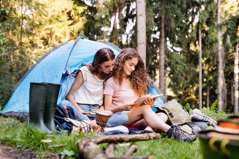 在帐篷前面的十几岁的女孩野营在森林里的 免版税库存照片