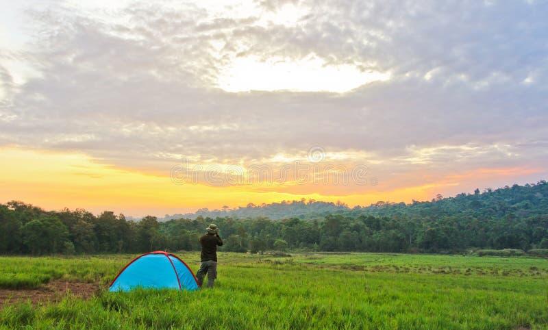 在帐篷旁边的人立场在草甸拍摄在他前面的风景照片 免版税图库摄影