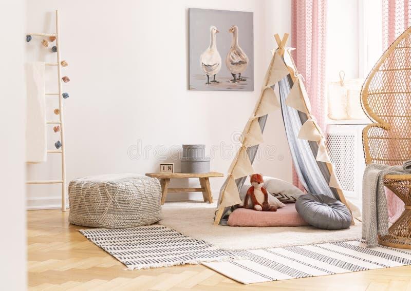 在帐篷旁边的柳条孔雀在斯堪的纳维亚人的椅子有枕头的和蒲团设计了女孩的游戏室,真正的照片 免版税库存照片