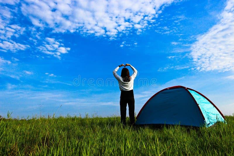 在帐篷旁边站立的妇女举起她的手象与宽天空蔚蓝和白色云彩的心形 免版税库存照片