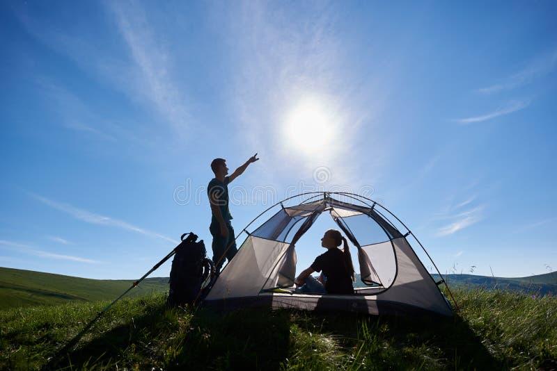 在帐篷的年轻对在明亮的太阳下的山假日在蓝天 免版税库存照片