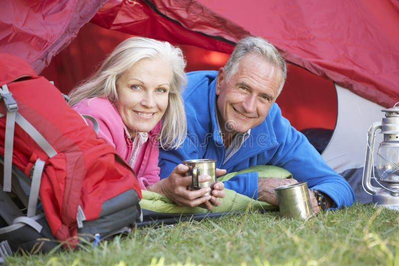 在帐篷里面的资深夫妇野营假日 图库摄影