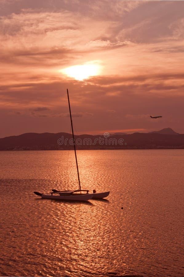 在帕尔马海湾的美好的日落视图与被停泊的风船和飞机 免版税库存图片
