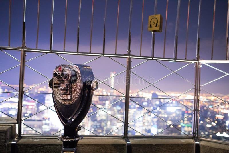 在帝国大厦顶部的双筒望远镜在晚上在曼哈顿 免版税库存图片