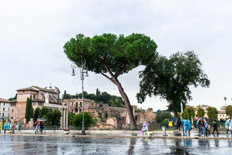 在帝国广场大道街上的人们沿着奥古斯都论坛Romanum论坛的废墟在罗马,意大利 免版税库存照片