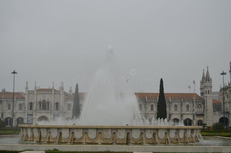 在帝国正方形的喷泉与贝拉母Jeronimos修道院他的后面的在里斯本 r 免版税库存照片