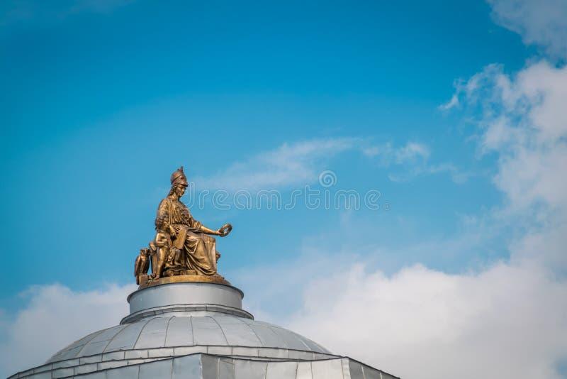 在帝国艺术学院大厦屋顶上面的金黄雕象在圣彼德堡,俄罗斯 免版税库存照片