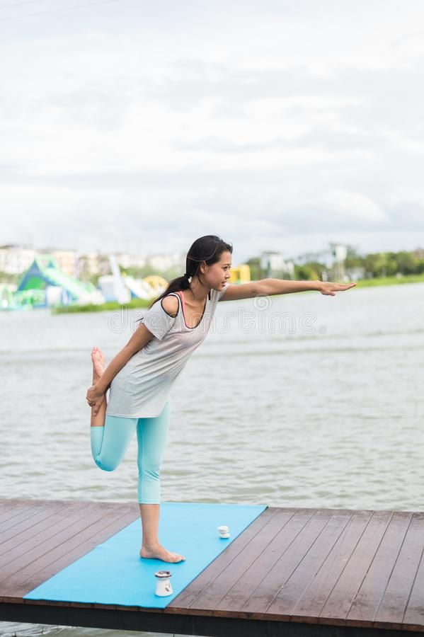 在席子的女子实践的瑜伽在盐水湖附近的公园 苹果概念卫生措施磁带 库存照片