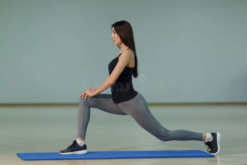 在席子的年轻有吸引力的微笑的女子实践的瑜伽在家 免版税库存照片