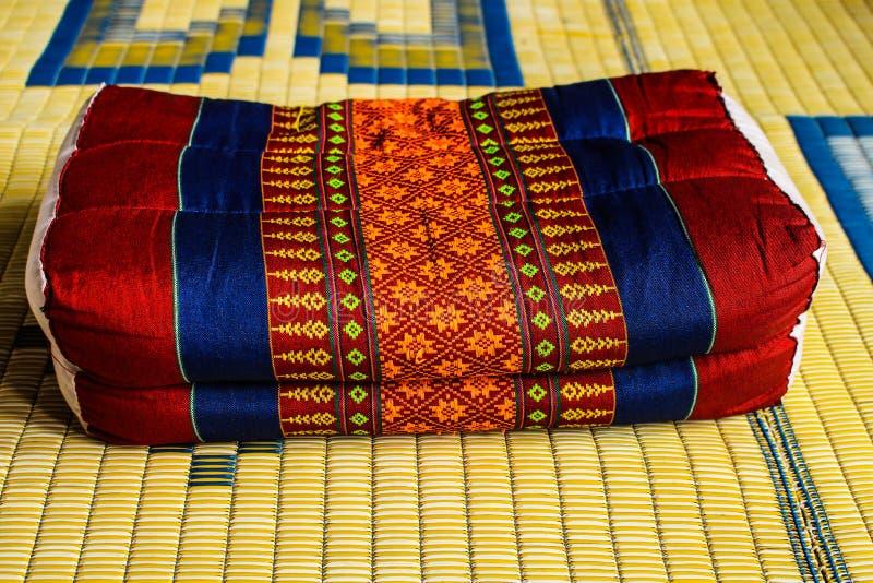 在席子的泰国老后面架靠背枕头 免版税库存照片
