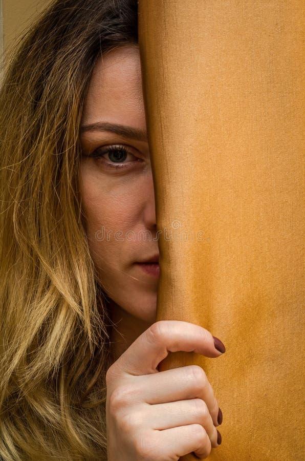 在帷幕后掩藏的一个年轻迷人的女孩的半面孔 免版税库存照片