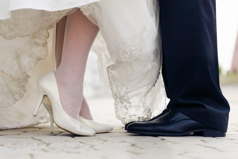 在常设新娘和新郎的婚礼鞋子 免版税图库摄影