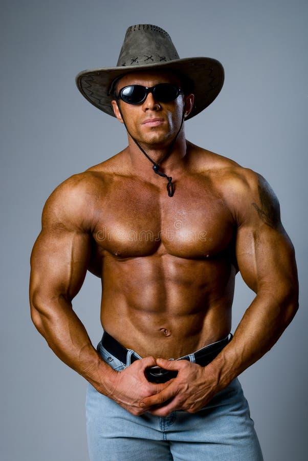 在帽子和太阳镜的肌肉男 免版税库存照片
