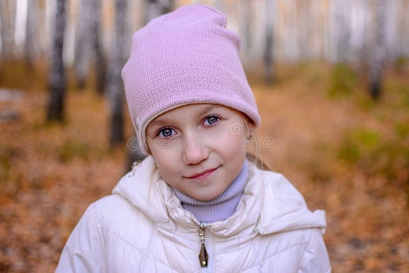 在帽子和夹克的秋天森林少年女孩站立反对背景一个女孩的画象有蓝眼睛的 免版税库存图片
