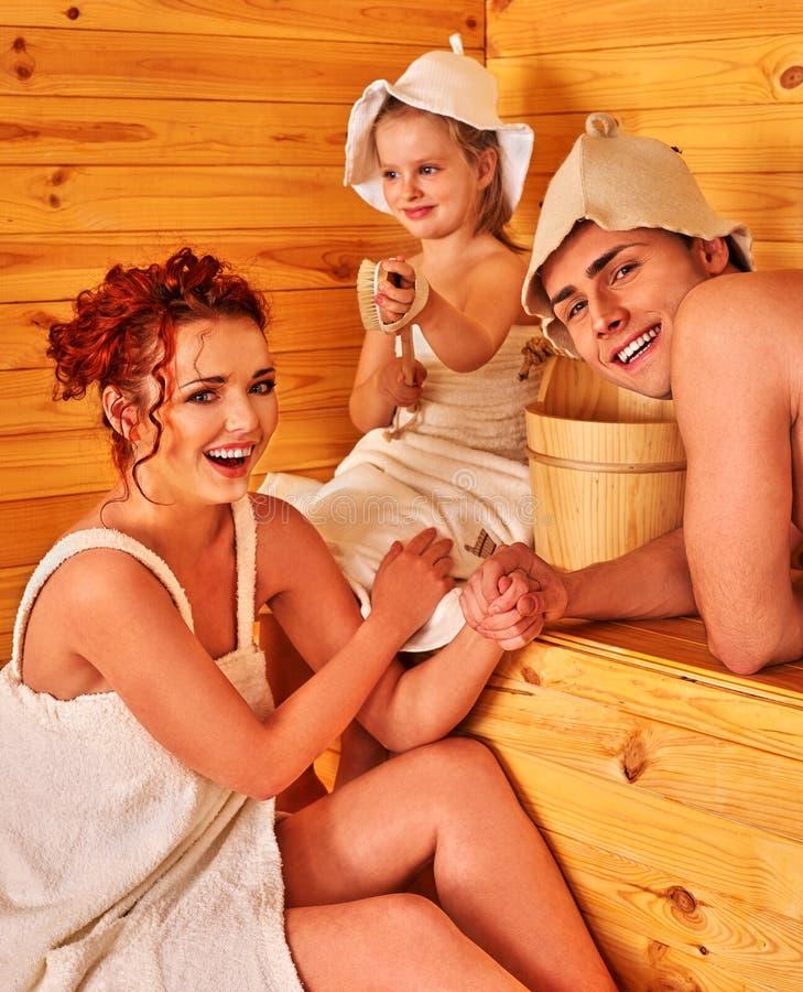 在帽子的愉快的家庭在蒸汽浴 免版税库存照片